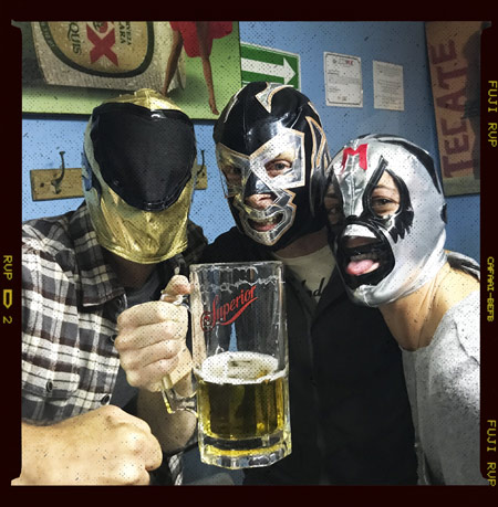 People drinking beer and wearing luchador masks