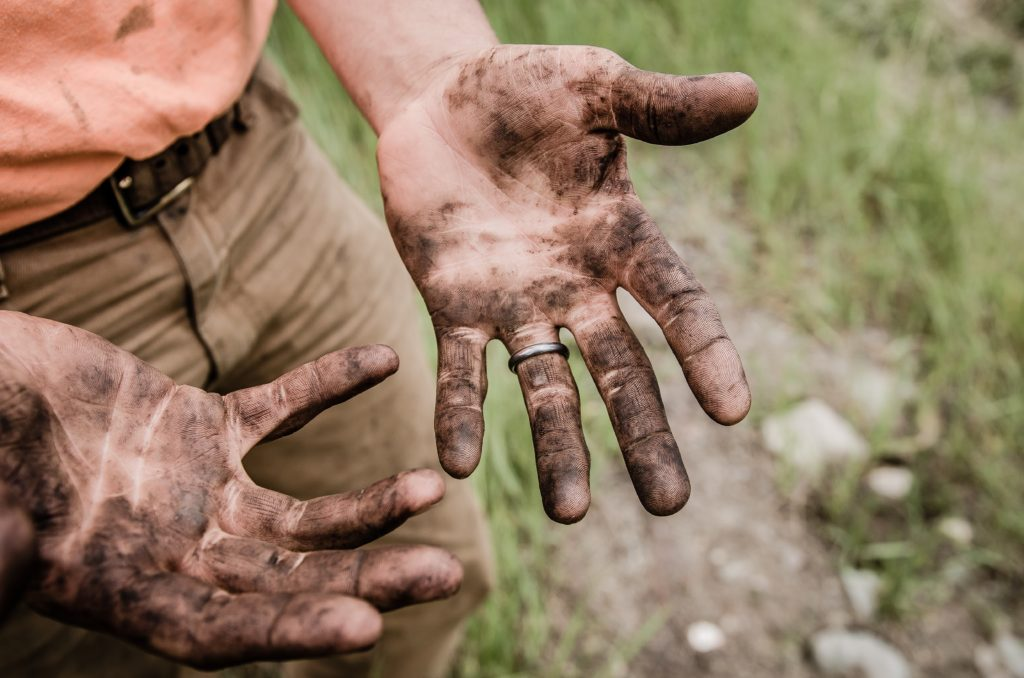 Photo of a dude with muddy hands